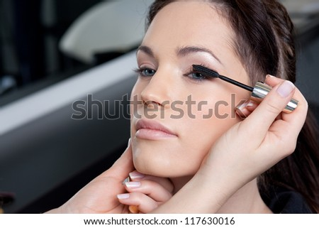 Make up artist applying mascara to a fashion model / bride - stock photo