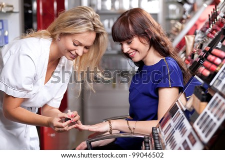 Make up artist applying nail polish in a beauty store. Selective focus. - stock photo