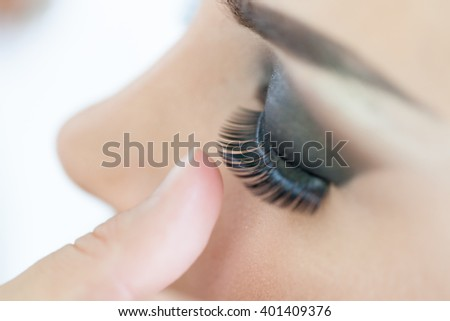 Make-up artist applying the false eyelashes to model. Close up. Selective focus