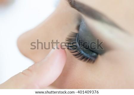 Make-up artist applying the false eyelashes to model. Close up. Selective focus - stock photo
