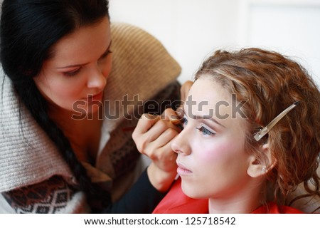 make up artist creating art make up on model's face - stock photo