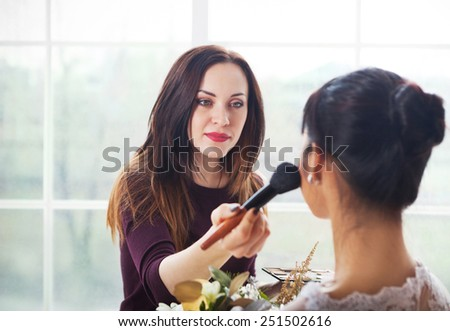 Make-up artist doing make up for young beautiful bride applying wedding make-up - stock photo