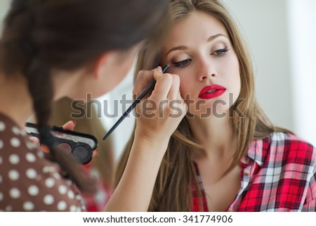 make up artist doing professional make up of young woman - stock photo