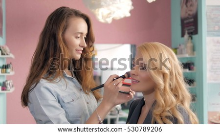 Make up artist doing professional   of young woman, brush in stylist hands.