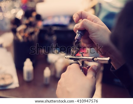 Make up artist filling the airbrush with liquid paint. Modern hipster colors - stock photo