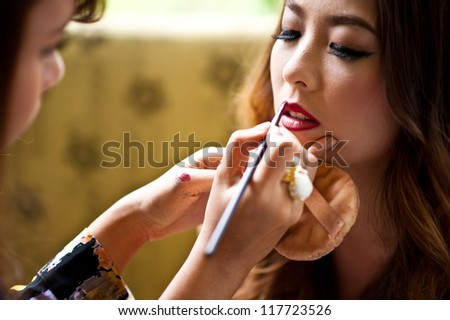 make-up artist lipstick on the mouth - stock photo