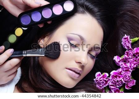 Make-up artist making eye visage to beautiful woman - stock photo