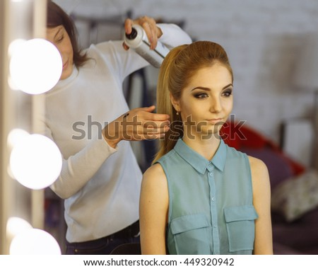 Make-up artist preparing model in a dressing room before photosession