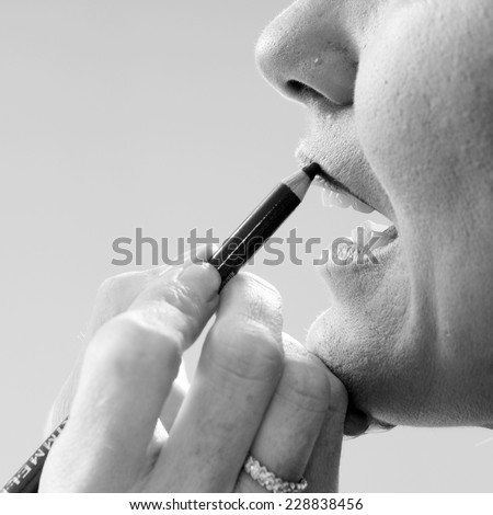 make up artist's hand close up applying lips line with a pencil to the model's mouth in black and white - stock photo