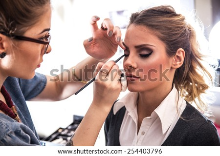 Make-up artist work on her friend.Real people. - stock photo