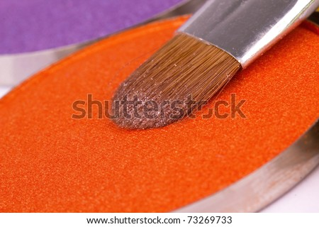 Make-up brush on professional orange eyeshadows palette, closeup - stock photo