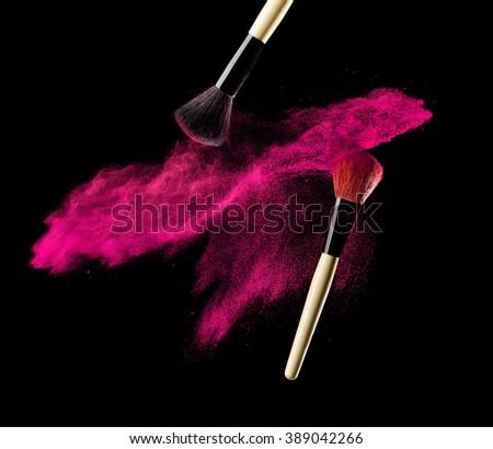 Make-up brush with pink powder explosion on black background - stock photo