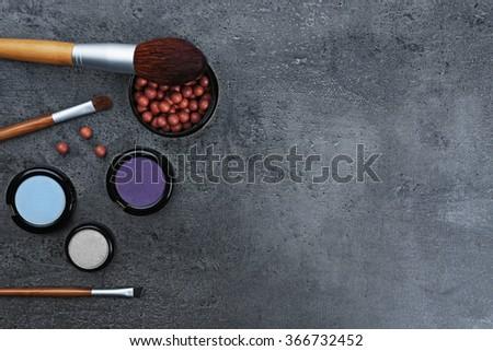 Make-up brushes, eye-shadow and blusher, on grey background - stock photo