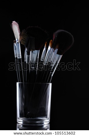 make-up brushes in glass cup on grey background