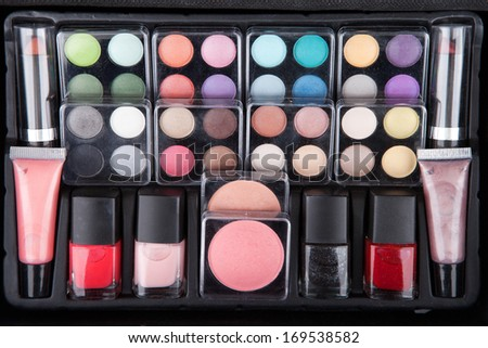 Make up case containing colorful eyeshadows, lipsticks, lip glosses, blushes and nail polishes - stock photo