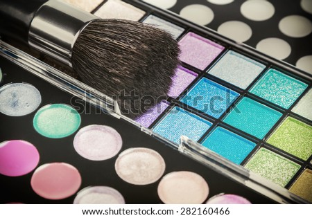 Make-up colorful eyeshadow palettes with makeup brushes. Focus in the middle of the frame on the blue shadows. Shallow depth of field. Toned image - stock photo