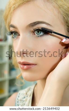 Make up. Cosmetic.Make-up artist applying mascara  on model's eye, close up. Applying Make-up.  - stock photo