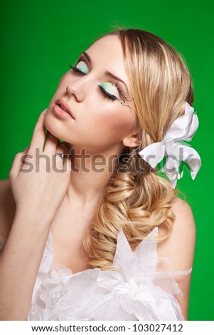 make-up on tender girl with closed eyes. studio shoot at green background - stock photo