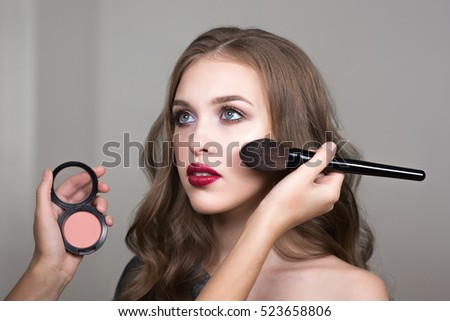 Make-up process, the face of a beautiful young woman and makeup artist's hands with a brush and blush. Cropped image