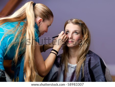 Make-up session - two young beautiful women - stock photo