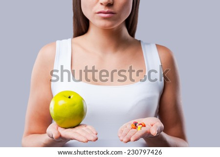 Make your choice!  Cropped picture of young woman holding an apple and pills in her hands - stock photo