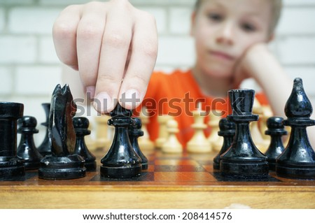 Make your move, boy plays checkmate - stock photo