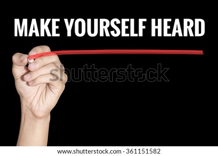 Make Yourself Heard word writing by men hand holding red highlighter pen on dark background - stock photo