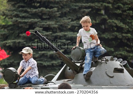 Makeevka, Ukraine - May, 9, 2012: Children on an armored vehicle during a parade in celebration of the anniversary of the victory over fascism - stock photo