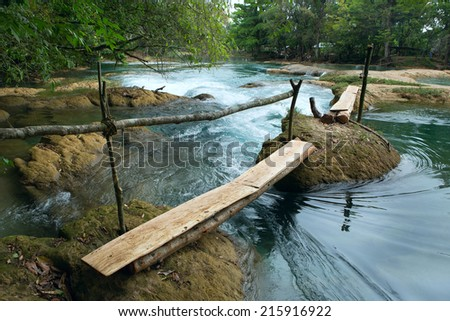 makeshift wood plank river crossing - stock photo
