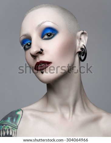 Makeup and beauty topic: punk girl with blue eyes and red lips on gray background in studio - stock photo