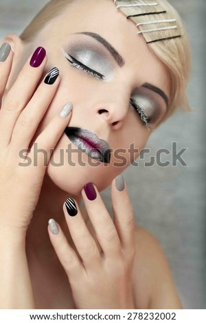 Makeup and manicure with grey shades and striped nail design.