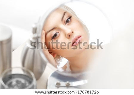 Makeup Applying. Beautiful Woman Looking at Her Face in the Miror Doing Daily Morning Makeup - stock photo