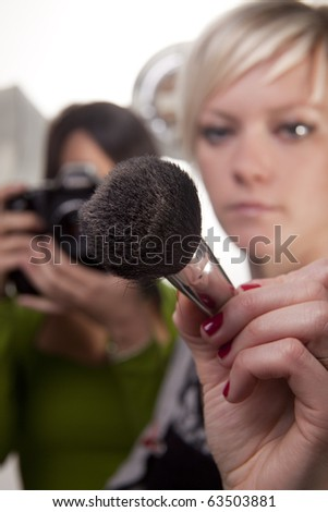 Makeup artist and photographer during a shoot with the makeup artist extending her brush to the camera. - stock photo