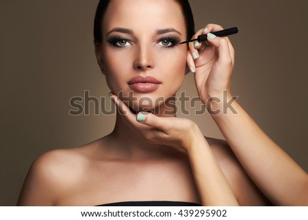 Makeup artist applies eye shadow. Beautiful woman face. beauty girl with Perfect make-up - stock photo