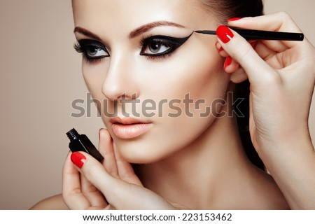 Makeup artist applies eye shadow. Beautiful woman face. Perfect makeup - stock photo
