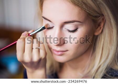 Makeup artist applying bright makeup - stock photo