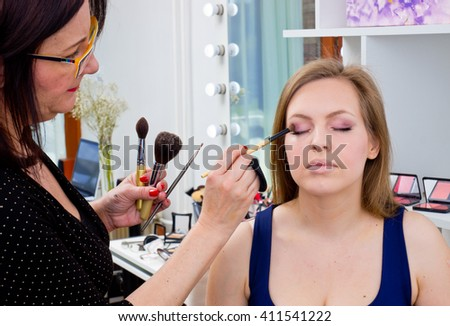 Makeup artist applying eyeshadow on attractive womans eyes in salon