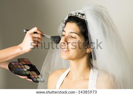 Makeup Artist applying makeup to a beautiful bride.  Horizontally framed shot. - stock photo