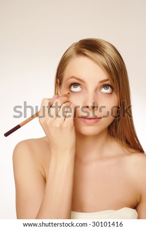 makeup artist applying mascara on the eyelashes of a beautiful girl. - stock photo