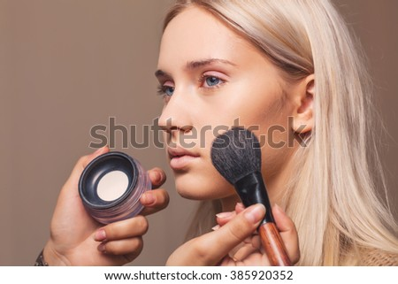 Makeup artist applying powder with make up brush - stock photo