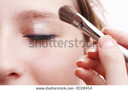 makeup artist applying silky eyeshadow with silver brush, beautiful young girl