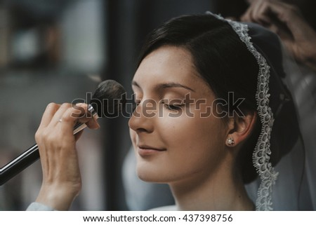 makeup artist doing makeup for the bride's - stock photo