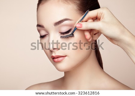 Makeup artist glues eyelashes. Beautiful woman face. Perfect makeup. Beauty fashion. Eyelashes. Cosmetic Eyeshadow - stock photo