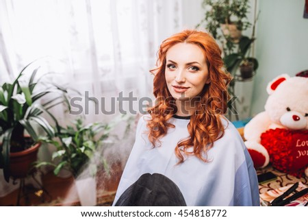 Makeup artist preparing bride before the wedding in a morning. Red hair woman. Hairdresser.