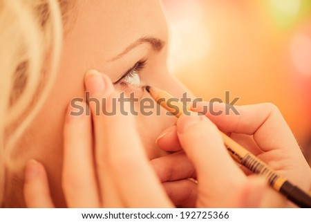 makeup artist with pen correcting eyelashes on woman eye