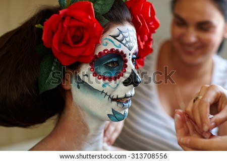 Makeup artists in work making a Halloween makeup - mexican Santa Muerte mask. - stock photo