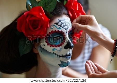 Makeup artists in work making a Halloween makeup - mexican Santa Muerte mask. - stock photo