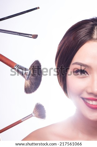 Makeup beauty Asian woman applying blush on face with brush tool. Make up girl looking at camera putting make-up on cheeks. Multi ethnic Chinese Asian / Caucasian female model isolated on white. - stock photo