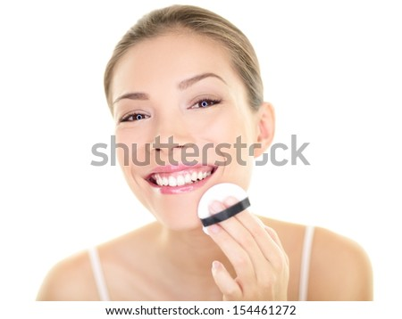 Makeup beauty Asian woman applying powder foundation on face. Beautiful healthy skincare girl putting make up getting ready looking in the mirror isolated on white background. Asian Caucasian model. - stock photo