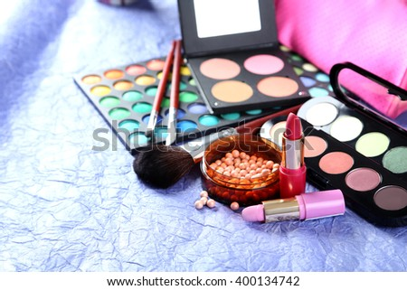 Makeup brush and cosmetics on a blue background - stock photo